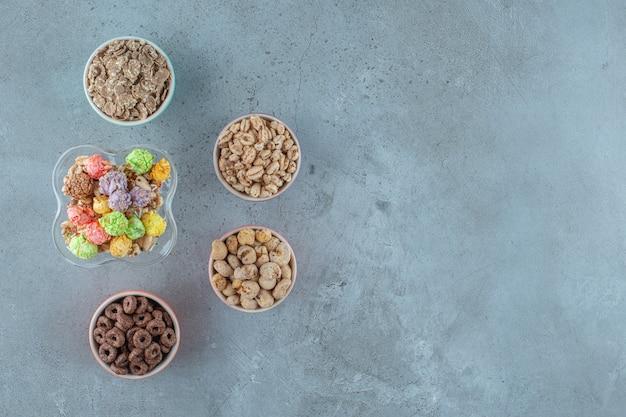 Cornflakes in een melkkoffieglas en kommen, op de blauwe achtergrond.
