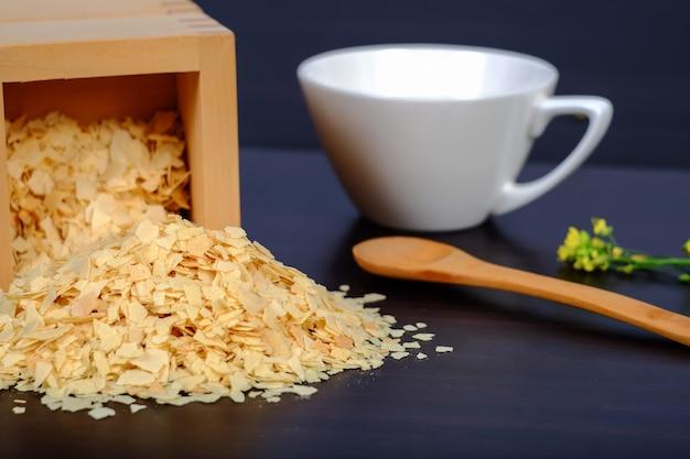 Cornflakes in houten vakje op een donker houten achtergrond en een exemplaar