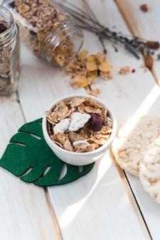 Cornflakes in kom dichtbij gemorste kruik granola en rijstcrackers op houten achtergrond