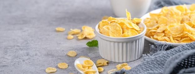 Cornflakes kom snoepjes met melk op grijze cement achtergrond, close-up, vers en gezond breakbast ontwerpconcept.