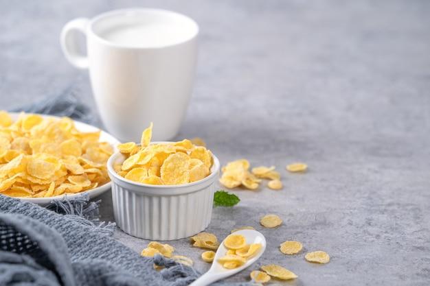 Cornflakes kom snoepjes met melk op grijze cement achtergrond, close-up, vers en gezond ontbijt ontwerpconcept.