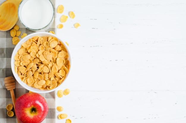 Cornflakes, melk en een appel op het tafelkleed