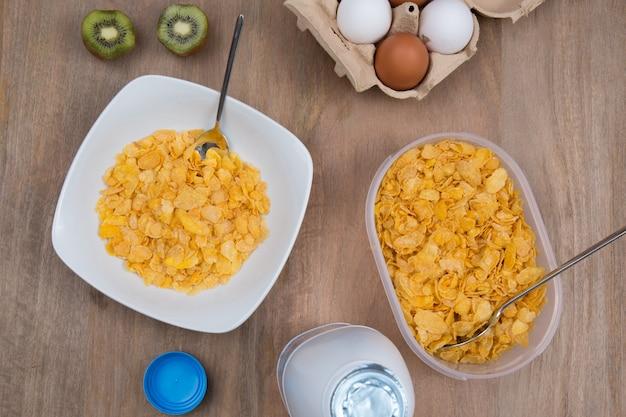 Cornflakes met melk en eieren op een houten bruine achtergrond