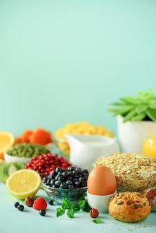 Cornflakes met melk, verse bessen, yoghurt, gekookt ei, noten, fruit, sinaasappel, banaan, perzik voor het ontbijt. gezond voedselconcept.