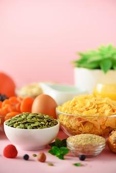 Cornflakes met melk, verse bessen, yoghurt, gekookt ei, noten, fruit, sinaasappel, banaan, perzik voor het ontbijt op gele achtergrond. ruimte kopiëren. gezond voedselconcept.
