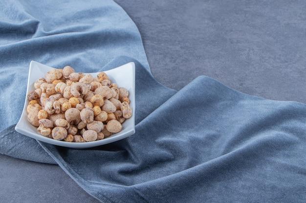 Cornflakes met muesli in een kom op een stuk stof, op de marmeren achtergrond.
