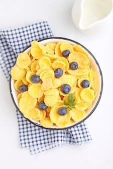 Cornflakes voor ontbijt met bosbessen op een witte achtergrond. selectieve aandacht.
