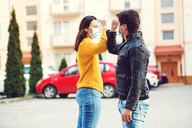 Corona-epidemie. jong koppel groeten met ellebogen buitenshuis. vrouw en man die gezichtsmasker in openlucht dragen.