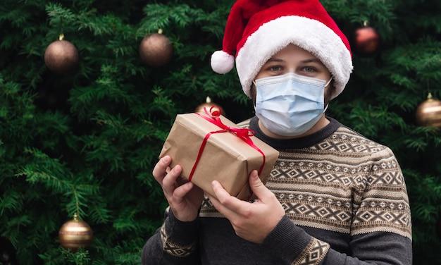 Corona kerst gefeliciteerd. portret man met kerstmuts en trui in medische masker, cadeau huidige doos met rood lint, kerstboom bokeh op achtergrond geven