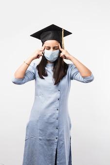 Corona pandemie en verwarring over universitaire examens in india - vrij indiase vrouwelijke student met verwarde uitdrukkingen met medisch gezichtsmasker en afstudeerhoed