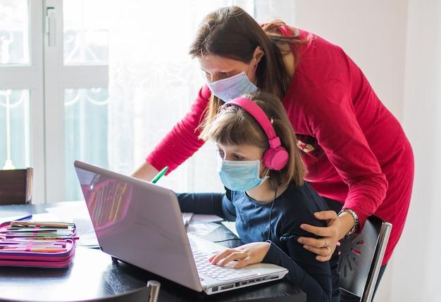 Corona-uitbraak. afsluiting en schoolsluitingen. moeder die haar dochter met gezichtsmasker helpt die online klassen thuis bestudeert.