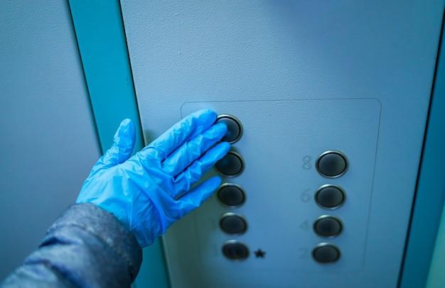Corona-uitbraak. hand met rubberen blauwe handschoen die op liftknoppen drukt. hygiëneconcept, preventie van bacteriën en virussen. zelfbescherming.
