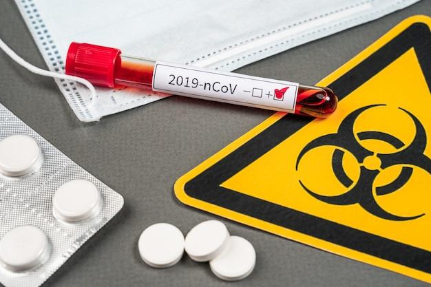 Corona-virus 2019-ncov-bloedbuis met handschoenen, masker en biologisch gevaarlijk zakje
