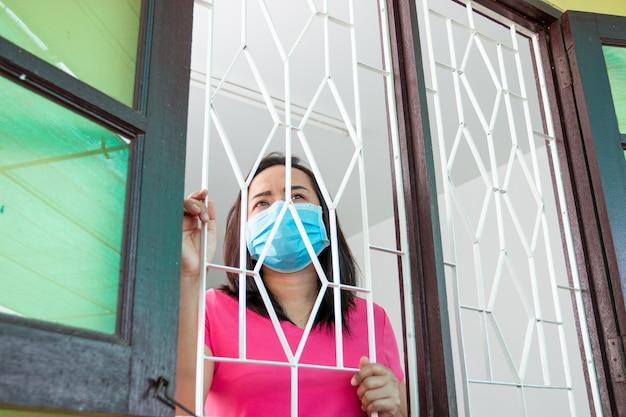 Corona-virus covid-19, tijdens detentie thuis gemaskerde vrouw zich verdrietig en eenzaam alleen thuis voelen soms gebruikt ze haar telefoon om videogesprekken te voeren met vrienden