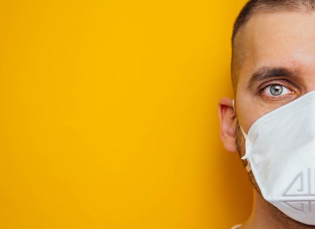 Corona-virus. jonge man in een gasmasker op een gele bescherming van de mond en ogen tegen virussen, infecties, uitlaatgassen. methoden voor het voorkomen van infectie.