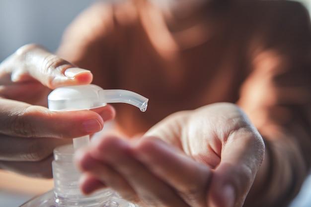 Corona-virusbescherming, close-up die haar handen reinigt met ontsmettingsgels, vrouw in quarantaine voor coronavirus die een beschermend masker draagt, thuiswerkend.