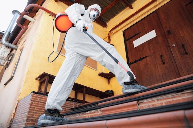 Coronapandemie. desinfector in een beschermend pak en masker spuit desinfecterende middelen in huis of op kantoor