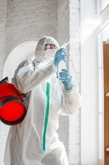 Coronapandemie. een desinfector in een beschermend pak en masker sproeit desinfectiemiddelen in huis of kantoor. bescherming tegen de ziekte van covid-19. preventie van het verspreiden van pneumonievirus met oppervlakken.