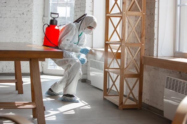 Coronapandemie. een desinfector in een beschermend pak en masker sproeit desinfectiemiddelen in huis of kantoor.