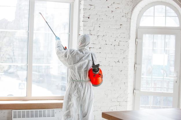 Coronapandemie. een desinfector in een beschermend pak en masker