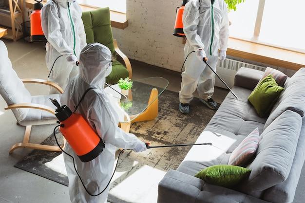 Coronapandemie. een ontsmettingsmiddel in een beschermend pak en masker sproeit ontsmettingsmiddelen in huis of kantoor. bescherming tegen de ziekte van covid-19. preventie van het verspreiden van pneumonievirus met oppervlakken.