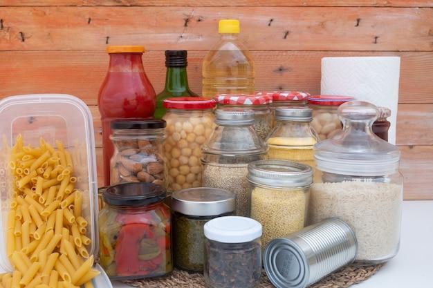 Coronapandemie. kleine voorraad voedsel voor de periode van isolatie in quarantaine. glazen potten met granen, peulvruchten, jam, pasta en rijst, blikjesned