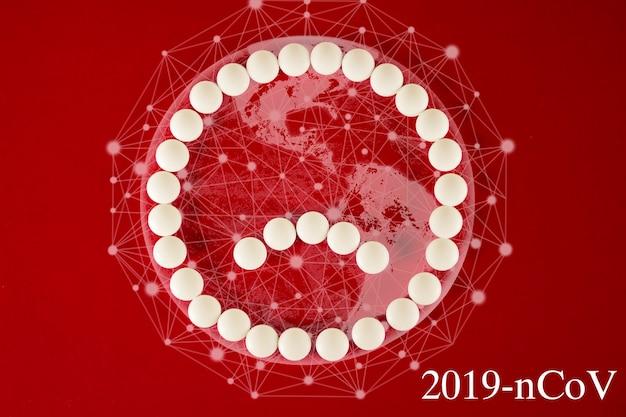 Coronavirus 2019-ncov nieuw coronavirusconcept dat verantwoordelijk is voor aziatische griep, pandemie van gevaarlijke griepstammen. triest smileygezicht gemaakt van witte pillen en virtuele hologram aarde op rode achtergrond.