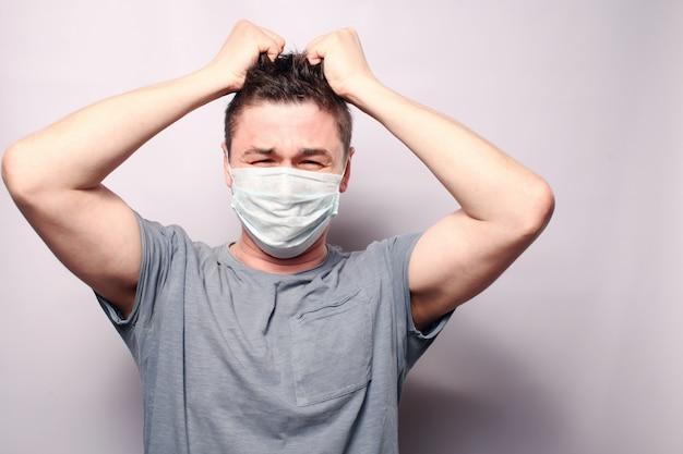 Coronavirus. 2019-ncov. roman coronavirus 2019. een man draagt een papieren ademhalingsmasker. de jonge man nam angstig zijn haar op.