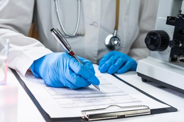 Coronavirus 2019-ncov-virus, de hand van een arts die bloedmonster vasthoudt en aantekeningen maakt bij het schrijven van patiëntgegevens op recept