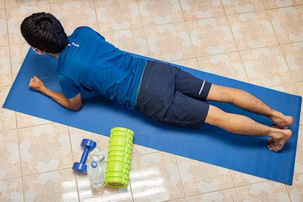 Coronavirus, aziatische man draagt een masker en oefent alleen in de kamer thuis om covid-19 te voorkomen. workout from home, oefening from home.