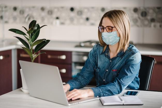 Coronavirus. bedrijfsvrouw die in huis werken, die beschermend masker in quarantaine dragen. blijf thuis. het meisje leert, gebruikend laptop computer in huisbureau. freelance. communicatie- en technologieconcept.