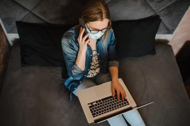 Coronavirus. bedrijfsvrouw die in huis werken, die beschermend masker in quarantaine dragen.
