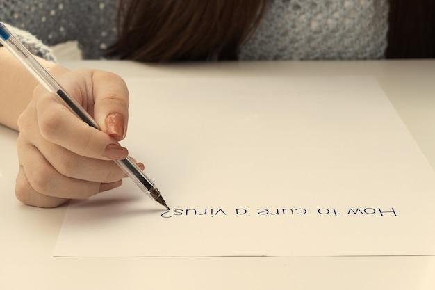 Coronavirus bescherming. vrouwelijke handen schrijven op een vel papier hoe ze een virus kunnen genezen
