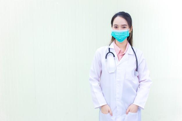 Coronavirus-beschermingsconcept een aziatische vrouwelijke arts die met zakkenroller staat
