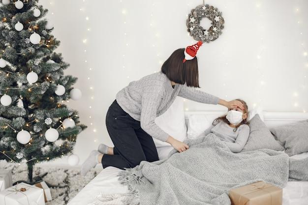 Coronavirus bij een kind. moeder met dochter. kind liggend in een bed. vrouw in een medisch masker.