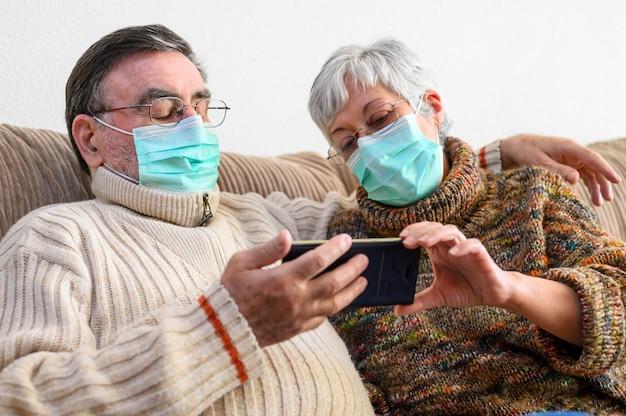 Coronavirus. blijf thuis, levensstijl. vrolijke bejaarde echtpaar zittend op een bank in een quarantaine thuis, een videogesprek met de smartphone. senior paar dragen van beschermende maskers.