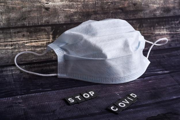 Coronavirus concept. wereldwijde oproep om thuis te blijven. medisch masker stop covid. masker met stop teken. coronavirus 19. coronavirus stopbord