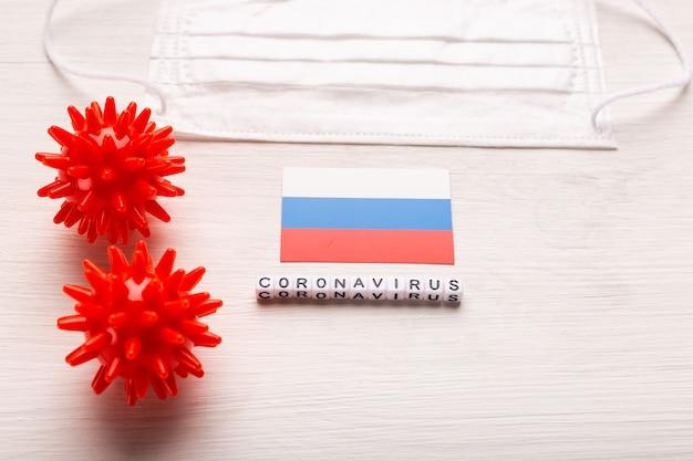 Coronavirus covid-19 concept. bovenaanzicht beschermend ademhalingsmasker en vlag van rusland. nieuwe chinese uitbraak van het coronavirus.