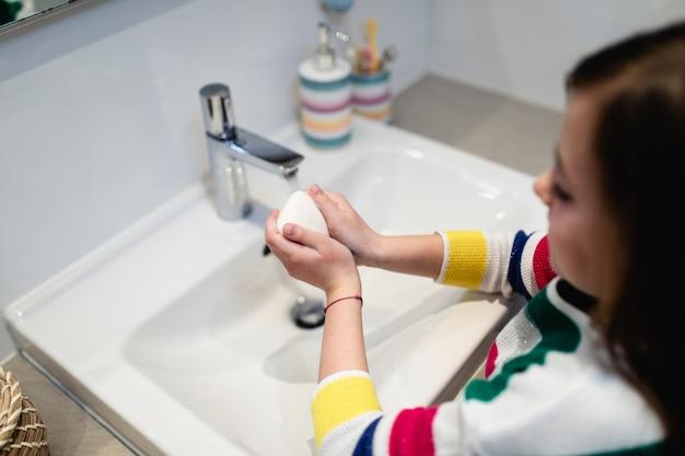 Coronavirus covid-19-concept. meisje wast haar handen in de badkamer met antibacteriële zeep.
