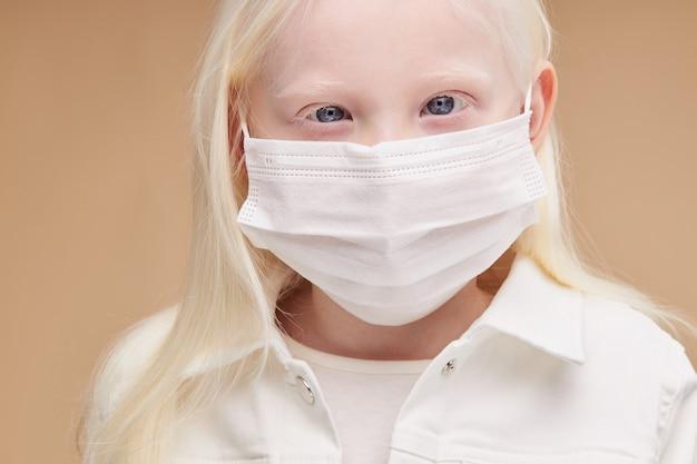 Coronavirus, covid-19 concept met weinig ongebruikelijk albinokind in geïsoleerd medisch masker