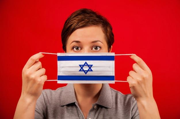 Coronavirus covid-19 in israël. vrouw in medisch beschermend masker met de afbeelding van de vlag van israël.