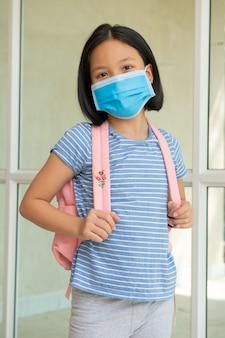 Coronavirus covid-19. online onderwijs. weinig aziatisch jong geitjemeisje dat gezichtsmasker draagt toont duimen voor dank u arts, gelukkig thuis. kind met gezichtsmasker gaat terug naar school na covid-19 quarantaine