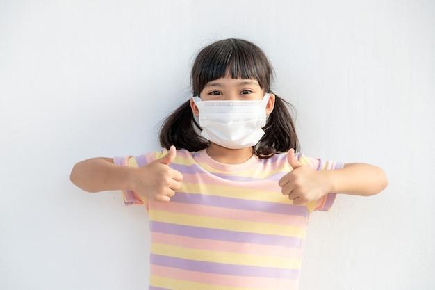 Coronavirus covid-19 pm2.5.online onderwijs.het kleine asain-meisje dat een gezichtsmasker draagt, laat thuis duimen voor goed en gelukkig zien. covid-19-coronavirus. blijf thuis. social distancing.nieuw normaal gedrag.