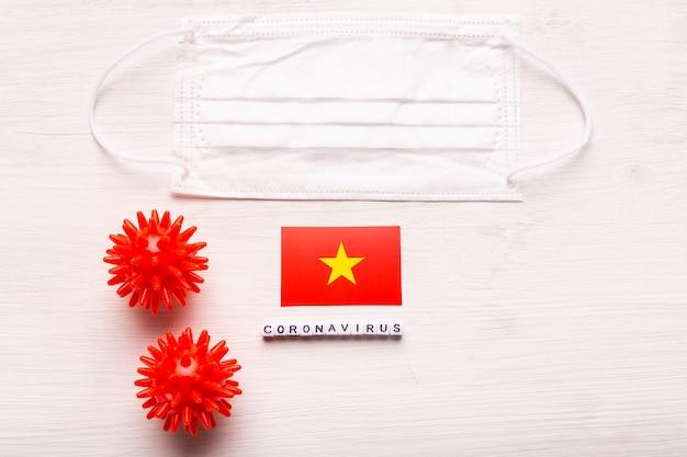 Coronavirus covid concept bovenaanzicht beschermend ademhalingsmasker en vlag van vietnam