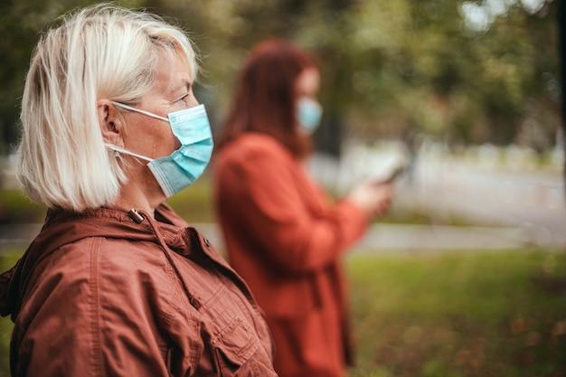 Coronavirus covid-epidemie. mensen dragen gezichtsmasker buiten in het herfstpark