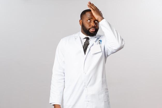 Coronavirus, covid19 en gezondheidszorgconcept. domme mensen. geërgerde en gehinderde afro-amerikaanse arts vertelt patiënten dat ze thuis moeten blijven tijdens het uitbreken van een pandemie, facepalm en rollende ogen