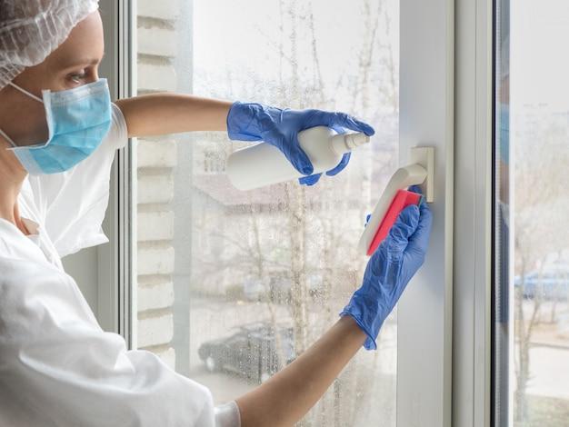 Coronavirus-desinfectie. mensen bij het maken van desinfectie op ramen. dokter in rubberen handschoenen desinfecteert raamkruk met desinfectiemiddel en sponzen