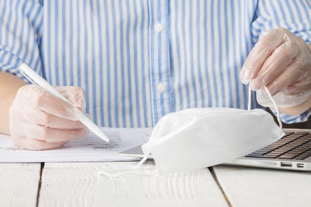 Coronavirus desinfectie van werkruimte reiniging desinfecterende doekjes om het toetsenbord af te vegen. stop de verspreiding van het coronavirus. vrouw met beschermende handschoenen die het toetsenbord schoonmaken.