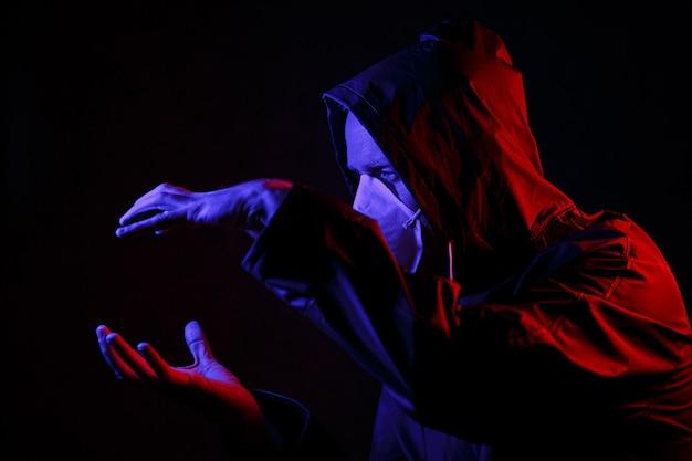 Coronavirus. een man met een masker en een chemisch beschermingspak in rood en blauw licht. strijd tegen het virus