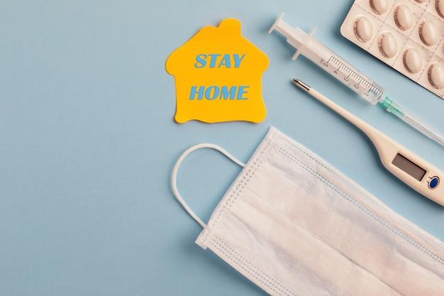 Coronavirus en blijf thuis concept. medische gezichtsmasker, thermometer, geneeskunde pillen en spuit